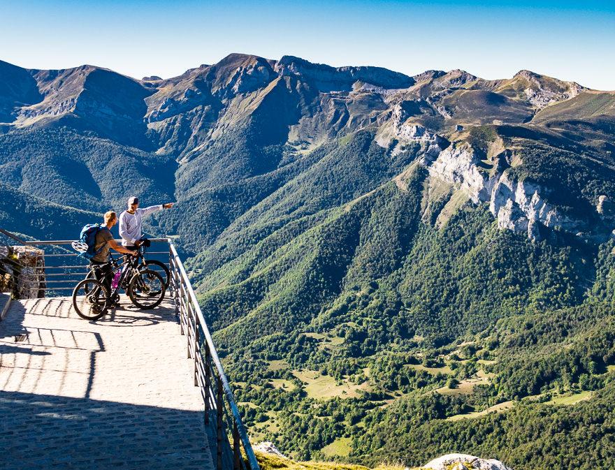 Two mountain bikers sightseeing Picos de Europa mountains